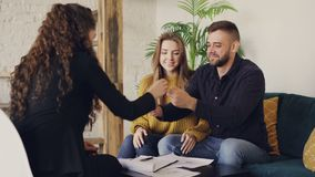 Young man is talking to housing agent, signing document and taking house key, clasping hands with realtor then kissing. His attractive wife. Buying real estate stock video footage