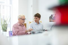 Young man talking to supervisor while he using caliper stock photos