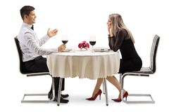 Young man talking to a young woman at a restaurant table stock photos