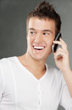 Young man talks by mobile phone. Beautiful young man in white clothes laughs and talks by mobile phone royalty free stock photos