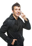 Young man talks by mobile phone. Beautiful young man in black clothes laughs and talks by mobile phone stock image