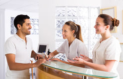 Young man talks with nurses. Young men talks with positive nurses in the medical office stock photos