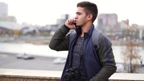 Young stylish man talks on the phone and smiles in the city slow motion stock video