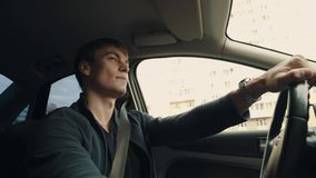 Young man talks to passenger while driving car through city street stock footage