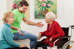 Young man tallking with two older women Royalty Free Stock Image