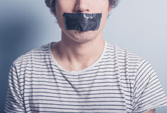 Young man with tape covering his mouth. A young man has a big piece of black industrial tape covering his mouth Royalty Free Stock Photo