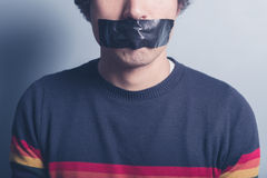 Young man with tape covering his mouth. A young man has a big piece of black industrial tape covering his mouth Stock Photos