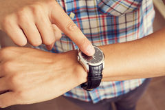 Young man tapping his finger on his wristwatch Royalty Free Stock Photos