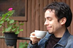 A Young Man Tastes Coffee. A young man having a cup of coffee at restaurant's terrace Royalty Free Stock Photography