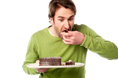 Young man tasting chocolate cake in hurry Royalty Free Stock Photography