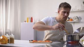 Young man tasting cooked food with disgusted face expression, funny grimacing. Stock footage stock footage