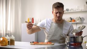 Free Young Man Tasting Cooked Food With Disgusted Face Expression, Funny Grimacing Stock Photography - 151821242