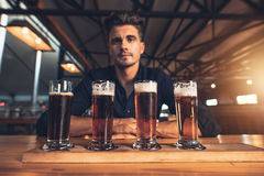 Young man tasting different varieties of craft beer. On a wooden table at brewery. Master brewer with different types of beers at bar table stock photography
