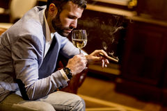 Young man tasting white wine and smoking cigar Stock Image
