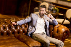 Young man tasting white wine and smoking cigar Royalty Free Stock Photo