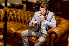 Young man tasting white wine and smoking cigar Royalty Free Stock Photos