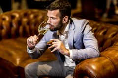 Young man tasting white wine and smoking cigar. In the room stock photography