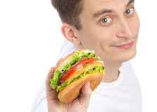Young man with tasty fast food unhealthy burger. In hand getting ready to eat isolated on a white background. Focus on hand with hamburger Stock Photography