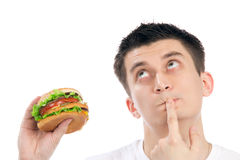 Young man with tasty fast food unhealthy burger Stock Images