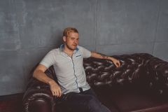 A young man with a tattoo on his hand posing on a leather couch. street style clothes: white shirt and black jeans. short hair and stock photography