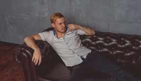 A young man with a tattoo on his hand posing on a leather couch. street style clothes: white shirt and black jeans. short hair and stock images