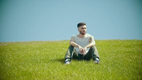 A young man with tattoos sitting on a bright green grass stock video
