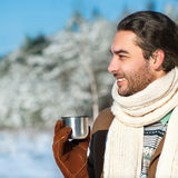 Young man with tea standing in snowy woods. Young attractive man drinking tea outside in winter time, close up portrait Royalty Free Stock Photography