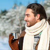 Young man with tea standing in snowy woods Royalty Free Stock Photos