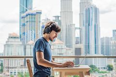 Young man teaches a foreign language or learns a foreign language on the Internet on her balcony against the backdrop of royalty free stock photography