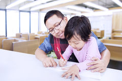 Young man teaches little girl to write Stock Image