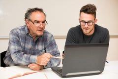 Young man teaching eldery man of usage of computer. Intergenerat Stock Image