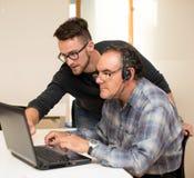 Young man teaching eldery man of usage of computer. Intergenerat Royalty Free Stock Images