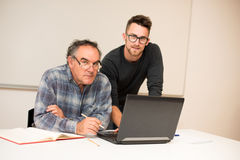 Young man teaching eldery man of usage of computer. Intergenerat Royalty Free Stock Photo