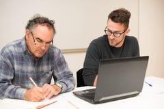 Young man teaching eldery man of usage of computer. Intergenerat Stock Photo