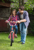 Young man teaching girl how to ride a bicycle at park. Young men teaching cute girl how to ride a bicycle at park royalty free stock images