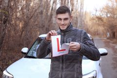 Young man tearing learner driver sign. While standing near car outdoors Royalty Free Stock Photography