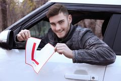 Young man tearing learner driver sign. While looking out of car window stock photos
