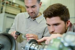 Young man in technical vocational training with teacher stock images