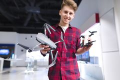 Young man is in the technology store with drones in his hands.man holds a quadcopter in his arms and smiles. A positive young man is in the technology store with stock image