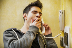 Young man or teenager answering the intercom. At the entrance in an apartment yawning Royalty Free Stock Photography