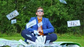 A young man, a teenager, in a business suit practices yoga in the park, sitting on a training mat. A young man in a business suit practices yoga in the park stock video