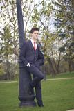 A young man, a teenager, in a classic suit. Relying on a vintage lantern in the park. Put your hands in your pockets. A young man, a teenager, in a classic suit Stock Photography