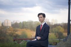 A young man, a teenager, in a classic suit. He sits on a large boulder in a spring park, his hands clasped on his knees. A young man, a teenager, in a classic stock images