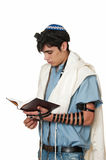 Young man in tefillin in profile. Young Sephardic Jewish man in tallit and tefillin does morning prayers Stock Image