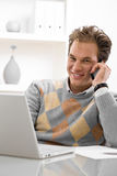 Young man telecommuting. Young man using laptop and calling on phone at home royalty free stock photo