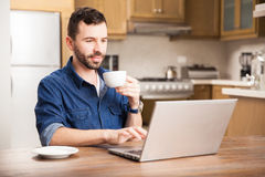Young man telecommuting. Attractive young Hispanic man enjoying a cup of coffee and using a laptop computer at home stock photo
