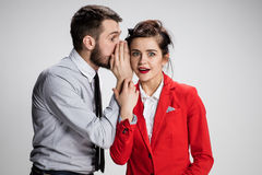 Young man telling gossips to his woman colleague at the office Royalty Free Stock Photography
