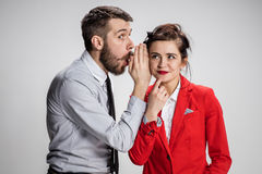 Young man telling gossips to his woman colleague at the office Royalty Free Stock Photo