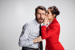Young man telling gossips to his woman colleague at the office Royalty Free Stock Image