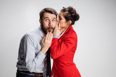 Young man telling gossips to his woman colleague at the office Royalty Free Stock Images